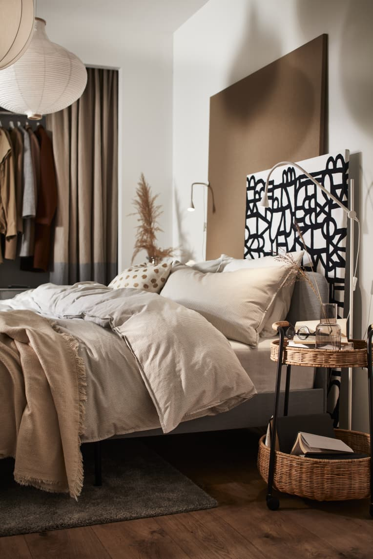 Bed with neutral linens and graphic headboard