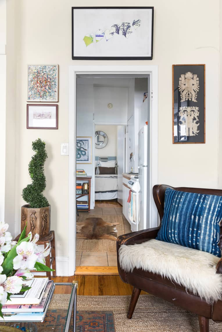 Doorway into kitchen framed by artwork. Leather chair in front of door.