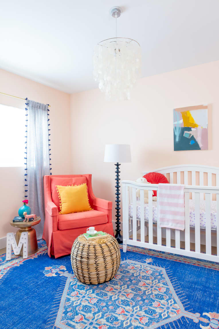 Nursery with blush walls and a blue carpet