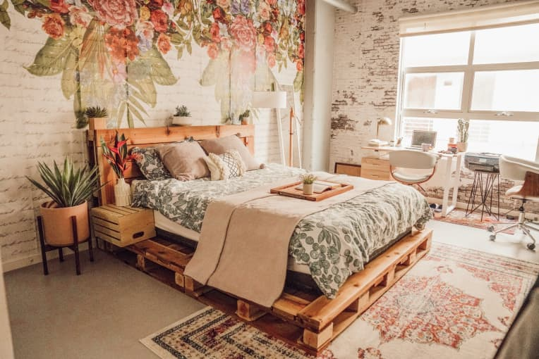Industrial loft with wood pallet bed, floral accent wall, and exposed brick