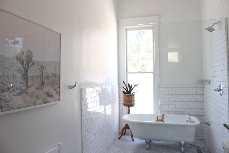 All white traditional bathroom with a clawfoot tub inside of a tiled shower