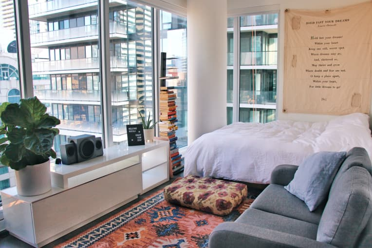 Bed with white linens and gray sofa in studio apartment