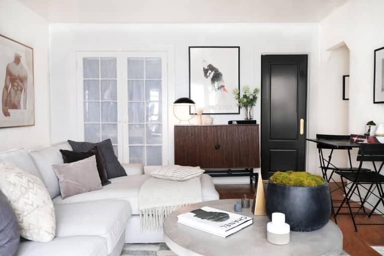 Living room with light gray sofa, black door, David Hockney print, and portrait of male body