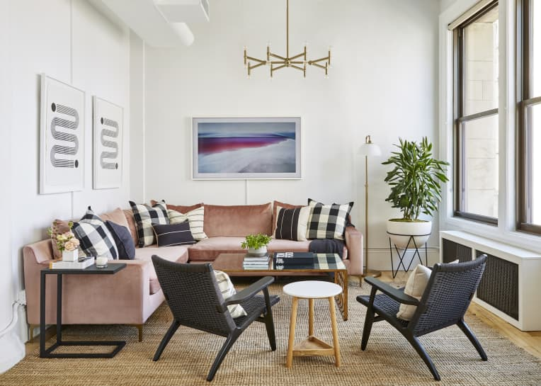 Living room with a pink sectional and black accent chairs