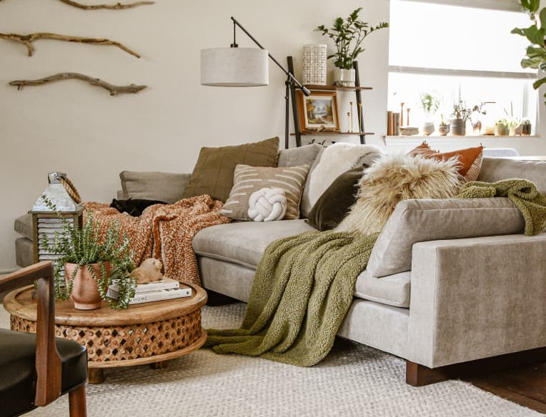 Gray sofa in living room with textured pillows and blankets