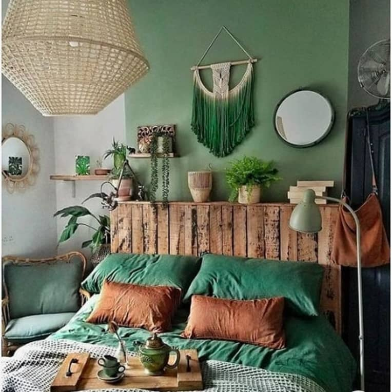 rustic pallet bed with headboard against a green wall
