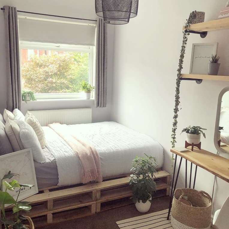 pallet bed with gray, white, and pink bedding, surrounded by plants and wood decor