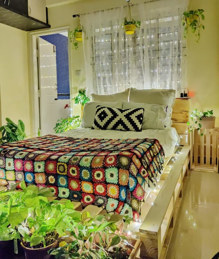 wood pallet bed lit by string lights, surrounded by plants