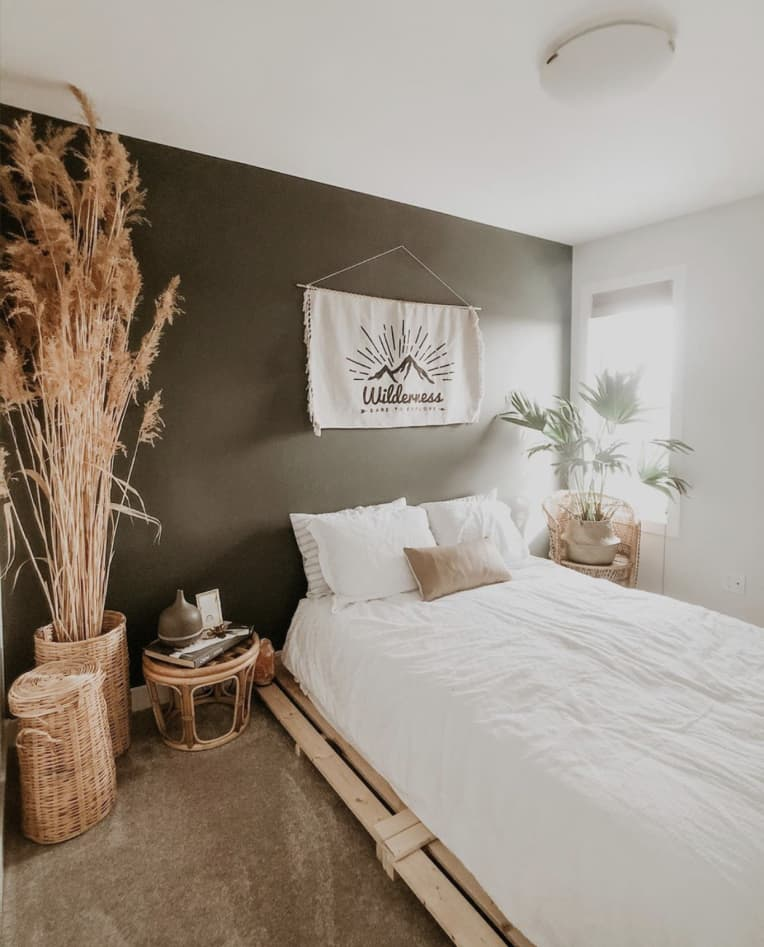 Wood pallet bed with white bedding against a deep green wall