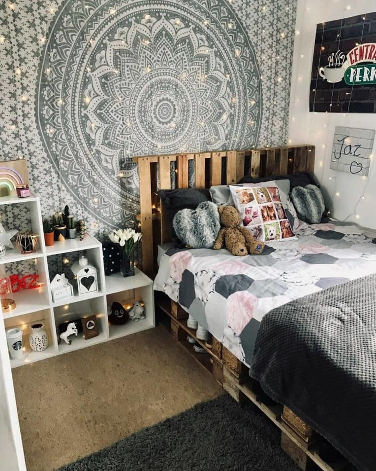 Pallet bed with headboard against a patterned wall hanging, with cube shelving next to it