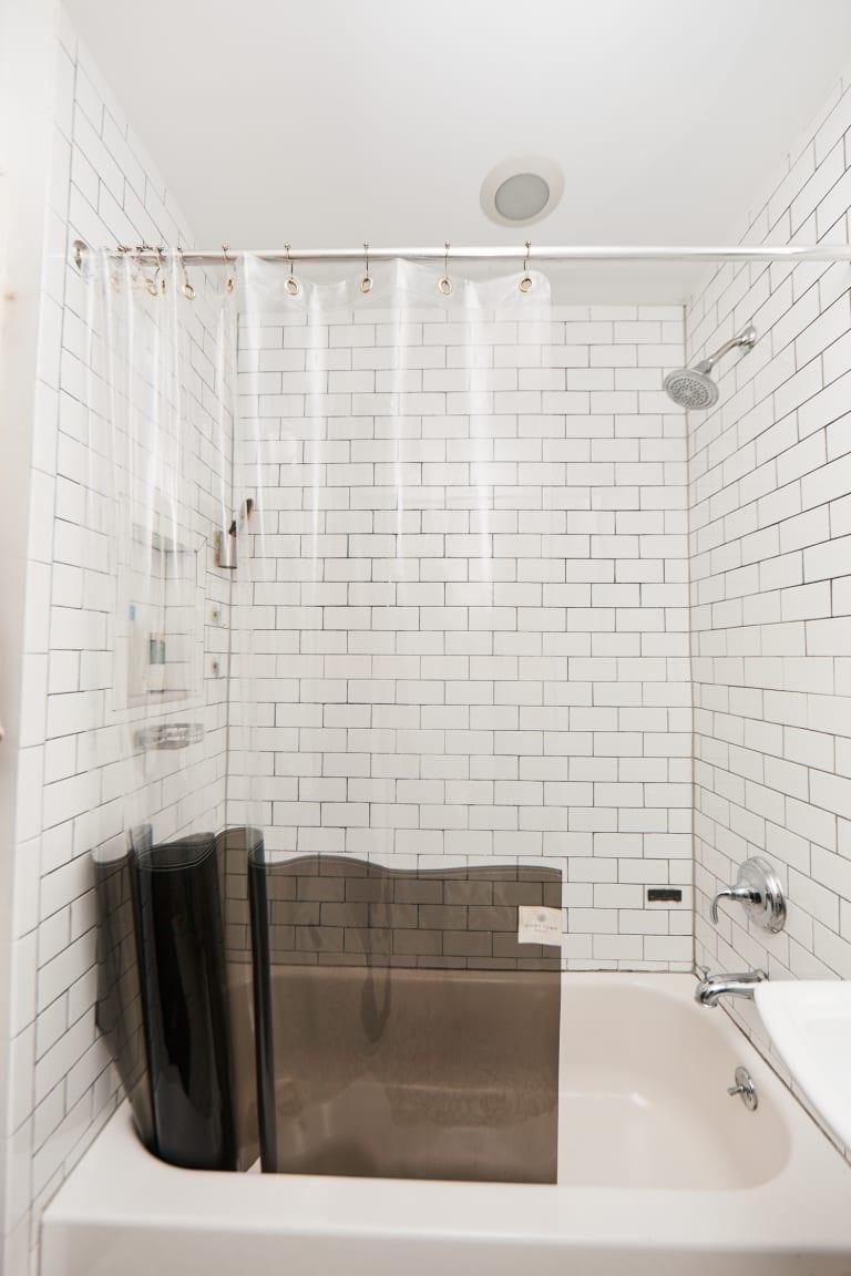 Clear shower curtain in a classic white bathroom
