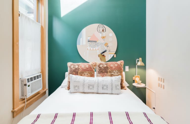 Small bedroom with bold green wall designed by The Sursey