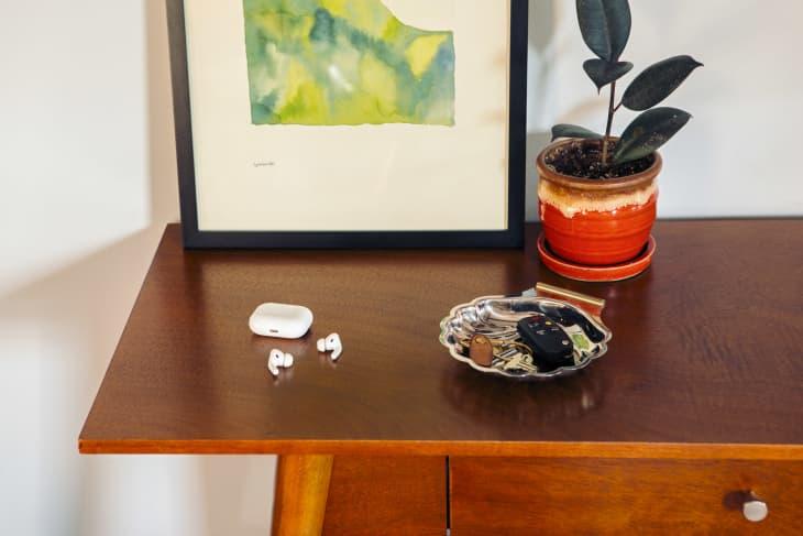 苹果耳机放在进门的木制桌子上,旁边是钥匙和一株室内植物