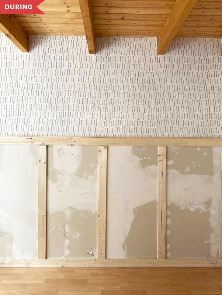 During: Wallpaper applied on top part of wall, with unfinished wood paneling applied on bottom