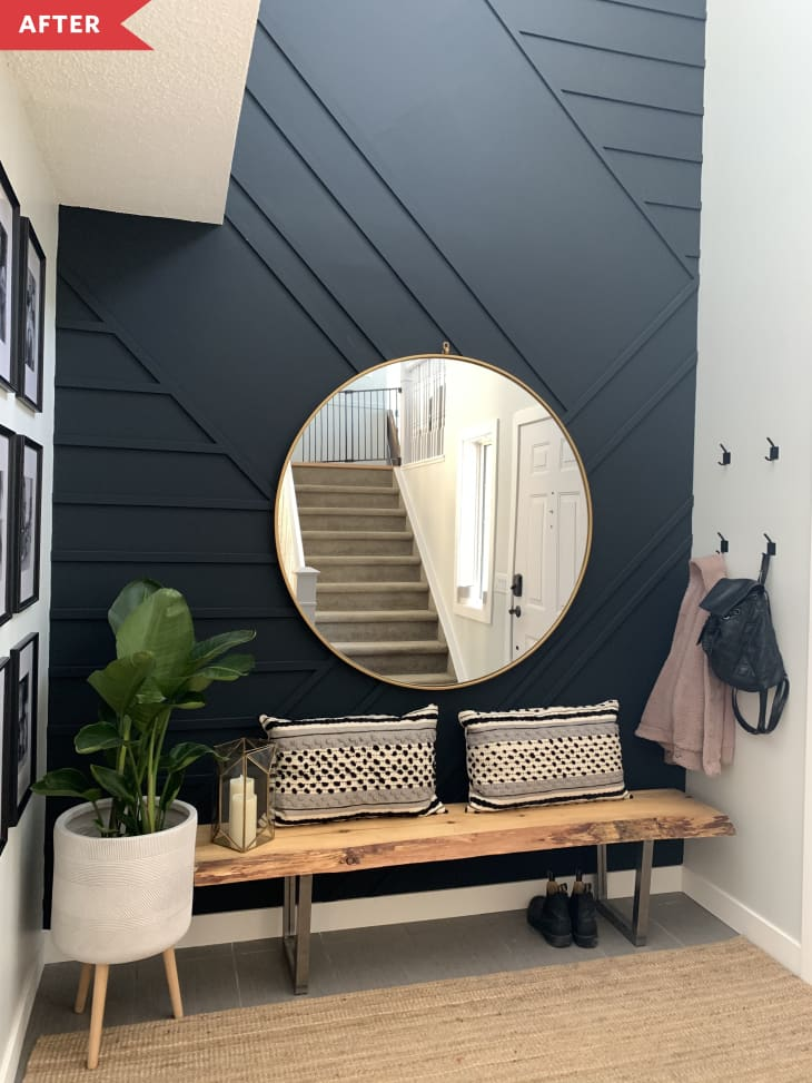 后:带有几何黑色墙壁、长凳、盆栽植物和镜子的入口通道