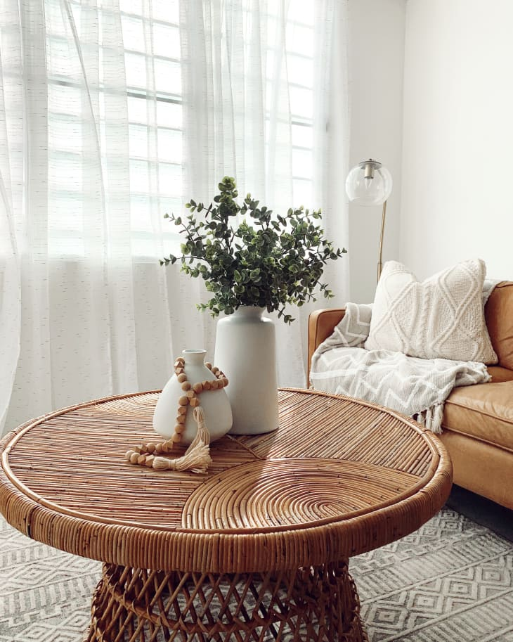 Circular brown wicker coffee table in front of leather sofa