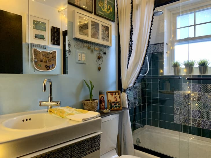 Bathroom with blue and green tiled shower and cat-shaped jewelry organizer