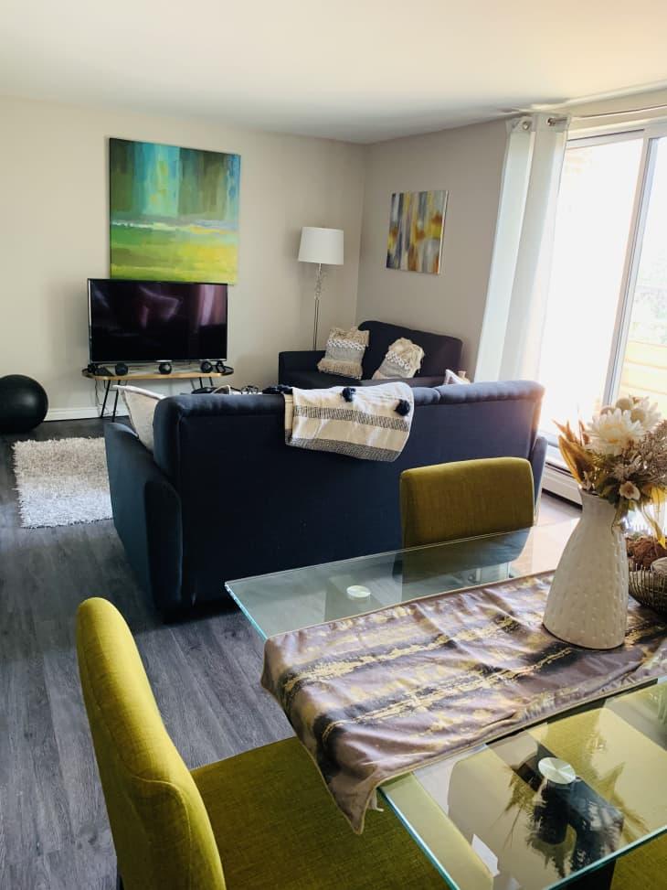 餐厅配有黄色餐椅和玻璃桌子,可以看到客厅