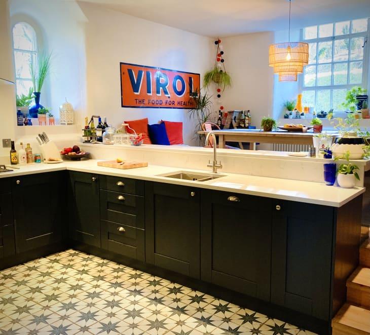 厨房配有星形图案瓷砖,黑色橱柜和视图与藤条吊坠和图形金属标志的餐厅