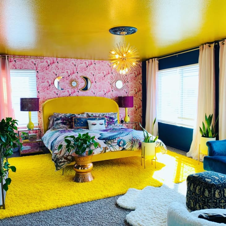 卧室有黄色地毯,黄色床,黄色天花板和粉红色的火焰壁纸