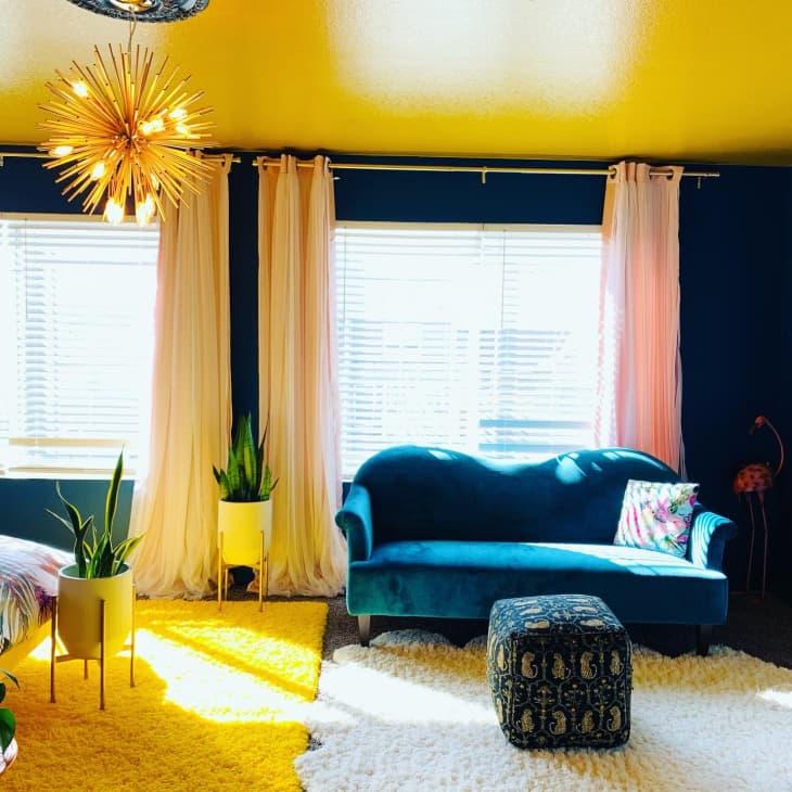 在窗口前面的蓝色天鹅绒Loveseat在有海军墙壁和黄色天花板的卧室