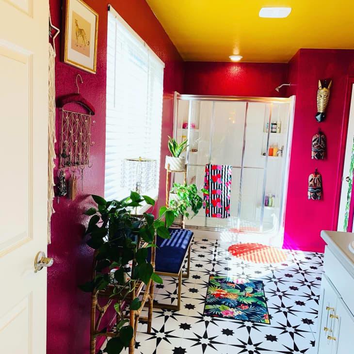 浴室配有fuscia墙壁,黄色天花板和黑色和白色瓷砖地板