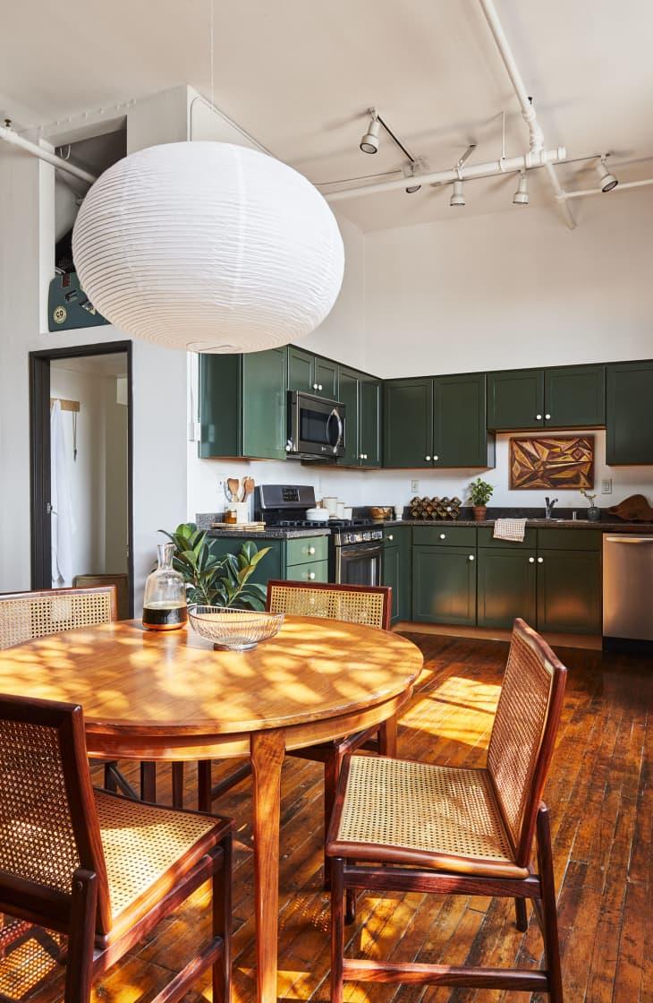 在圆的木餐桌上的白色灯笼垂饰光与厨房看法有绿色内阁的在背景中