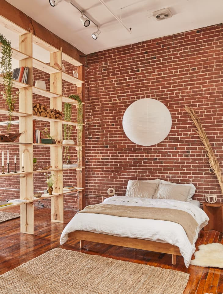 垂悬在床上的白色地球灯笼在与暴露的砖墙上的睡眠区域