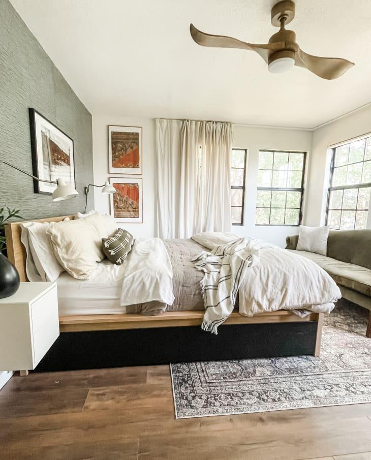 舒适,通风的卧室与绿色纹理的墙壁和绿色天鹅绒沙发对面的床脚