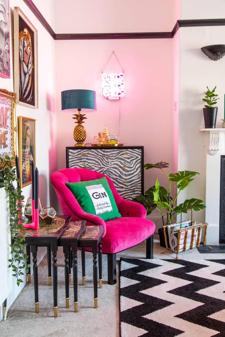 粉红色的椅子在客厅的角落有雪佛龙地毯的