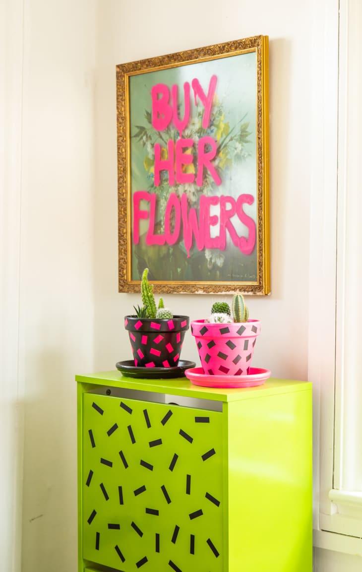 """在艺术品下的黄绿色橱柜说""""买她的花"""""""