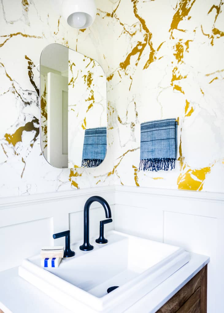 Half bathroom with marble wallpaper and frameless mirror