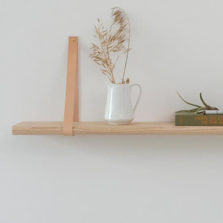 Leather strap floating shelf accessorized with neutral decor