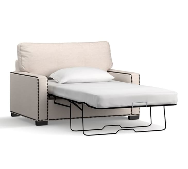Sleeper arm chair in a tan color with nailhead trim