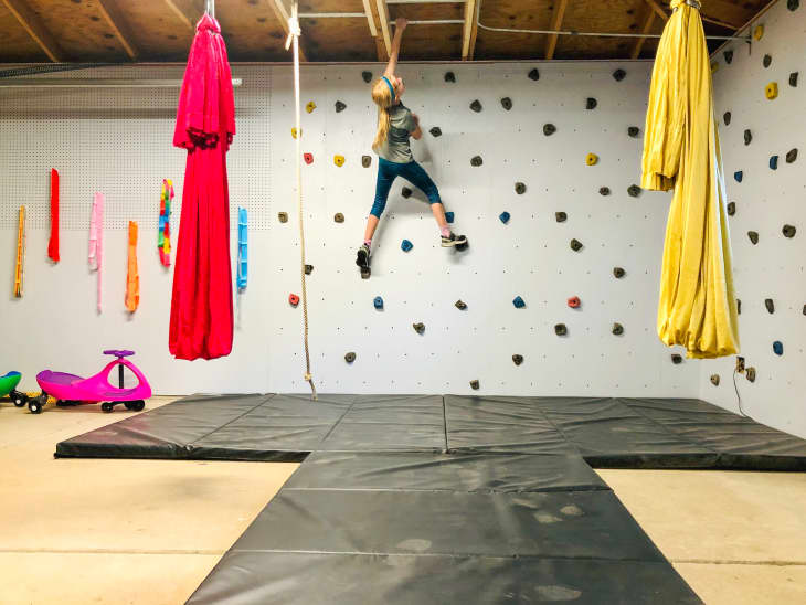 Girl climbing wall handholds in garage over mats with hanging hammocks