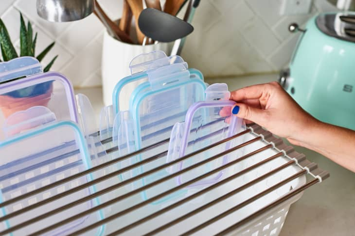 A person placing a container lid into a drying rack with other lids.