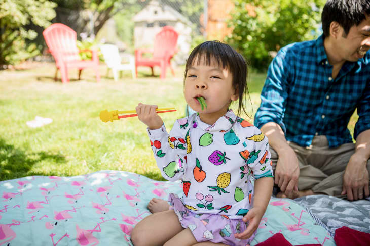 埃莉诺拿着筷子吃着青豆
