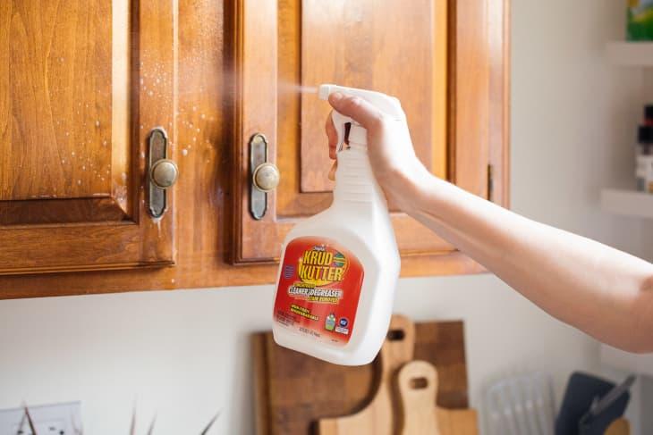 Someone spraying Krud Kutter on kitchen cabinets