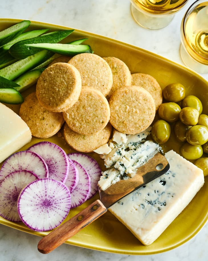ranch shortbread nibbles sit on a board with cheese, olives, cucumber and radicchio