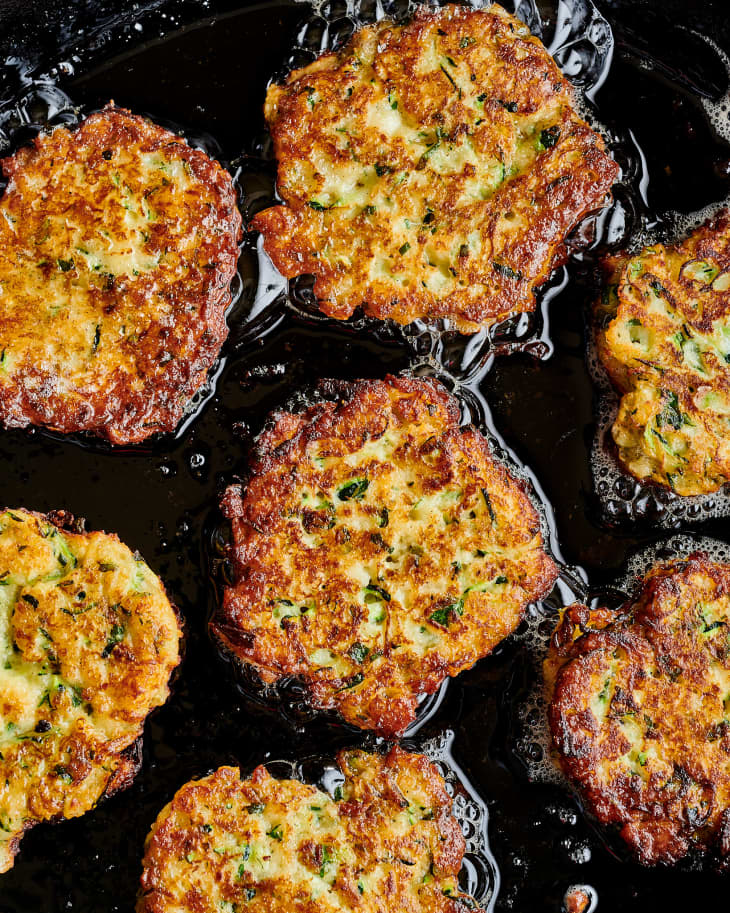 close up of zucchini fritters sizzling in pan