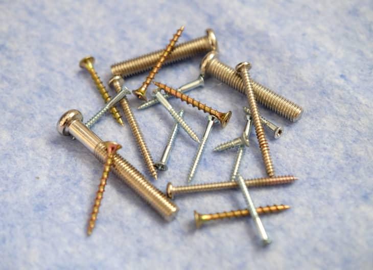 一堆金、铜和银的螺丝放在灰色的柜台上