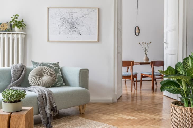时尚斯堪的纳维亚客厅设有设计薄荷沙发,家具,嘲笑海报地图,植物和优雅的个人配饰。现代家居装饰。开放空间与用餐室。