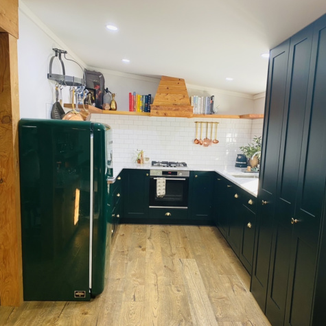 A New Zealand Bungalow Has a Neat Shelf Divider and a Gorgeous Green Kitchen